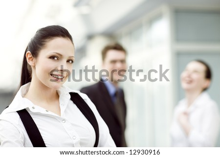 Portrait of young smiling woman with two happy people in background - stock photo