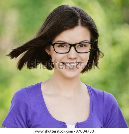 Portrait of young smilling woman wearing violet blouse ang eyeglasses standing at summer green park. - stock photo
