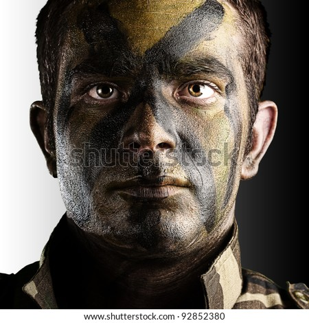 portrait of young soldier face with jungle camouflage paint against a white and black background - stock photo