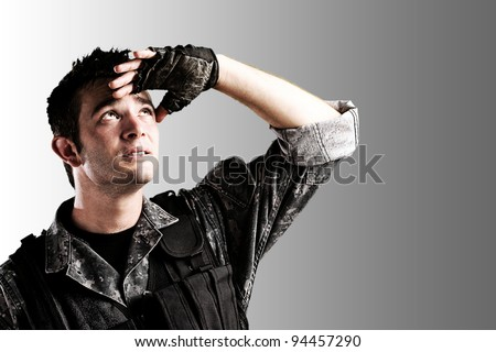 portrait of young soldier handsome looking up against a grey background - stock photo