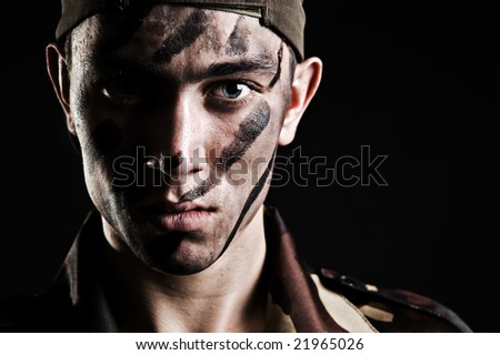 portrait of young soldier in camouflage against black background - stock photo