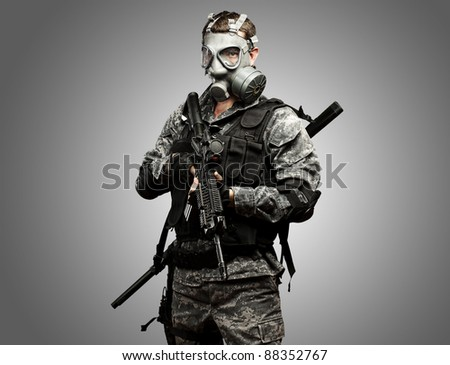 portrait of young soldier with gas mask and rifle against a grey background - stock photo