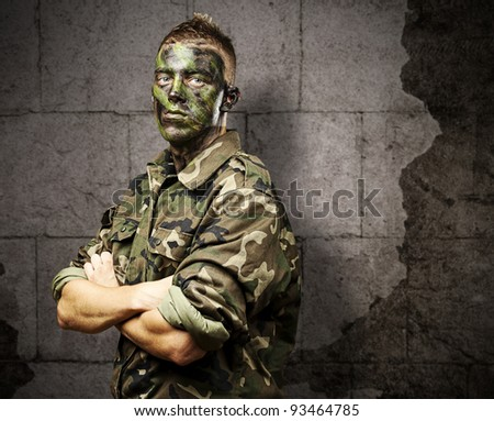 portrait of young soldier with jungle camouflage paint against a grunge bricks background - stock photo