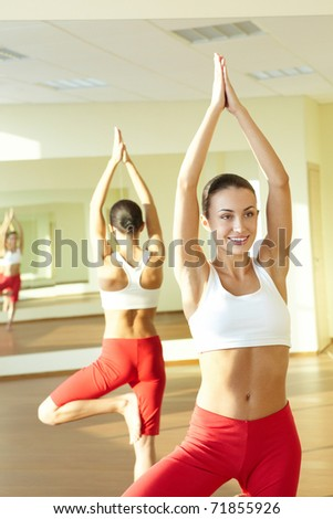 Portrait of young sporty girl doing physical exercise in front of mirror - stock photo