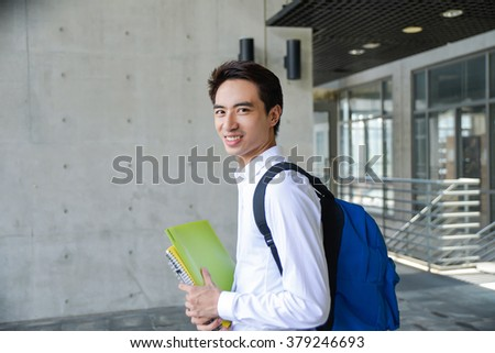 portrait of young student holding book at campus - stock photo