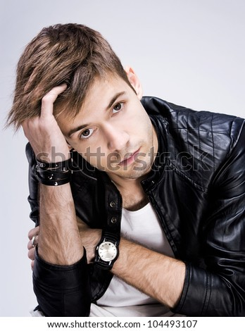 Portrait of young stylish guy with the watches and accessories on a light grey background - stock photo