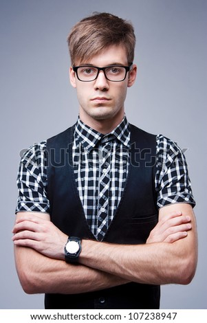 Portrait of young stylish man in glasses and with wristwatch on a gray background - stock photo