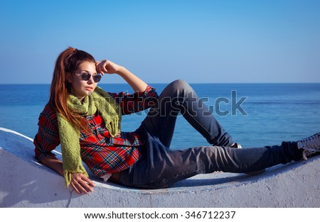 Portrait of young stylish woman taking rest near the sea.Outdoor fashion portrait of hipster teenager, wearing denim jeans,shirt and sunglasses,posing near sea at rainy day, romantic , vintage style. - stock photo