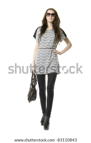 Portrait of young stylish woman with in sunglasses walking on white background - stock photo