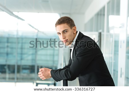 Portrait of young successful and confident businessman. Man looking at camera and standing in nice modern building. Office interior - stock photo