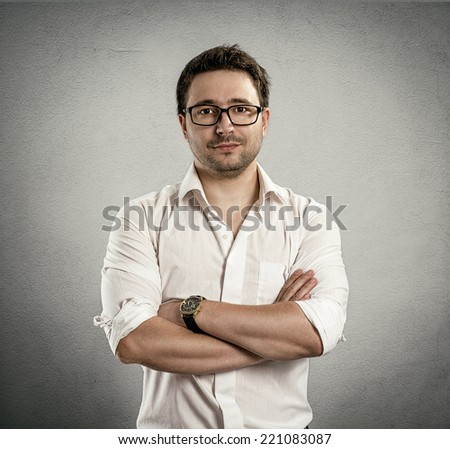 Portrait of young successful business guy in stylish eyeglasses over grey background. Handsome Caucasian man  wearing white shirt and spectacles posing in studio.  - stock photo