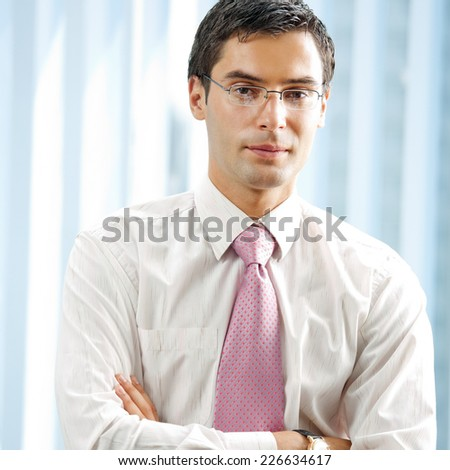 Portrait of young successful businessman at office - stock photo
