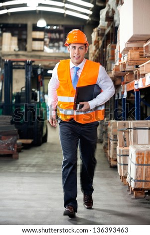 Portrait of young supervisor in a hurry at warehouse - stock photo