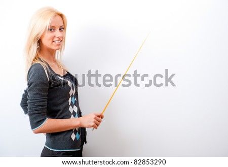 Portrait of young teacher pointing on white marker board in modern educational center - stock photo