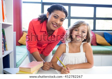 Portrait of young teacher with girl in school library - stock photo