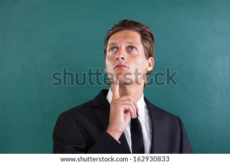 Portrait Of Young Thoughtful Businessman Looking Up - stock photo