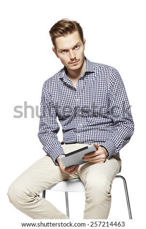 Portrait of young  thoughtful man holding a tablet. - stock photo