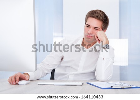 Portrait Of Young Tired Businessman Sitting In Office - stock photo