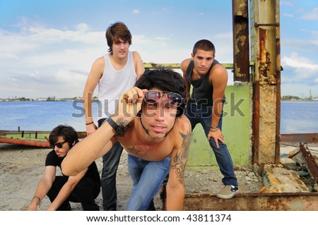 Portrait of young trendy team of male friends posing on grunge urban background - stock photo