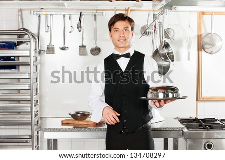 Portrait of young waiter with cloche lid cover and tray standing in commercial kitchen - stock photo