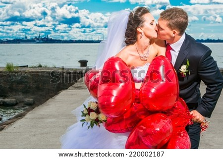 portrait of young wedding couple on seashore, beautiful bride with groom with red balloons, summer nature outdoor - stock photo