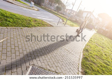 Portrait of Young Woman and Her Shadow in the Morning. The Girl is Looking at Camera. The Park is in a Residential Area, there are some Houses on Background. - stock photo