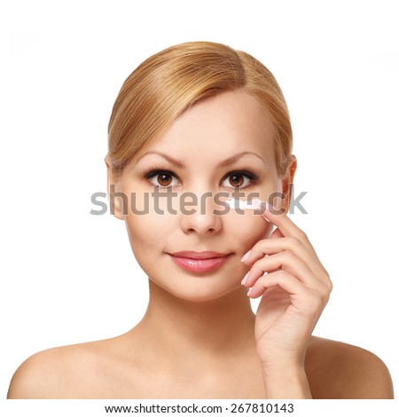 Portrait of young woman applying cream on her pretty face isolated on white - stock photo