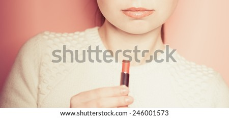 portrait of young woman applying lips make up.  Vogue style - stock photo