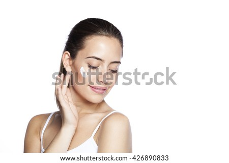 Portrait of young woman applying moisturizer cream on her pretty face. Isolated on white background - stock photo
