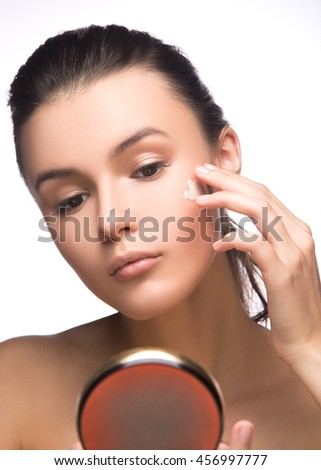 Portrait of young woman applying moisturizer cream on her pretty face - white background. fashion and beauty - stock photo