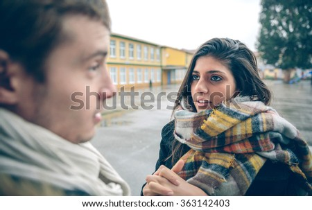Portrait of young woman asking apologize to offended man after a hard quarrel outdoors. Couple relationships and problems concept. - stock photo