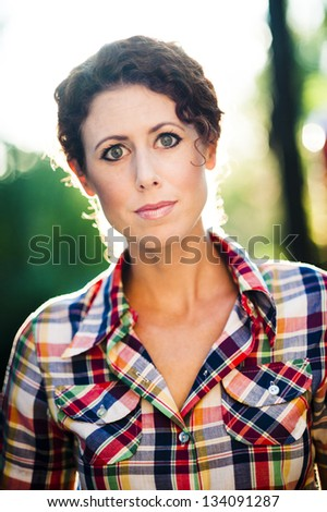 portrait of young woman back lit by the sun - stock photo