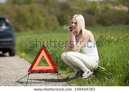 Portrait Of Young Woman Calling For Help To Repair Car - stock photo