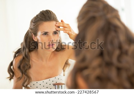 Portrait of young woman checking facial skin condition - stock photo