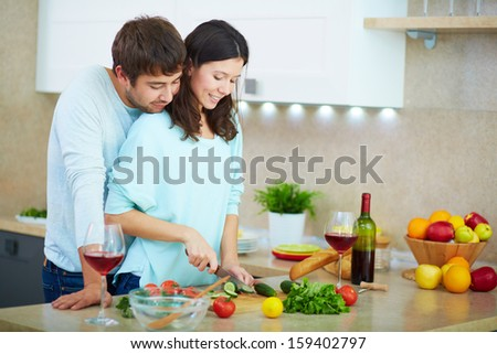 Portrait of young woman cooking salad with her husband near by  - stock photo