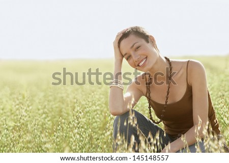 Portrait of young woman crouching in field of grass - stock photo