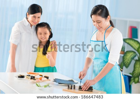 Portrait of young woman cutting sushi rolls in the kitchen with her mother and daughter on background - stock photo