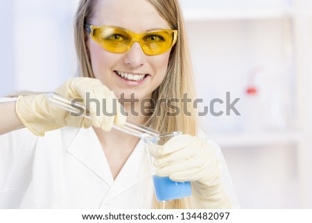 portrait of young woman doing experiment in laboratory - stock photo