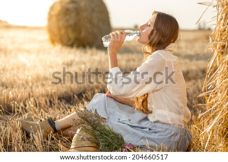 Portrait of young woman drink water bottle at summer sunny field. Sunshine, glow sun - stock photo
