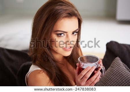 Portrait of young woman drinking tea at home sitting on sofa. - stock photo