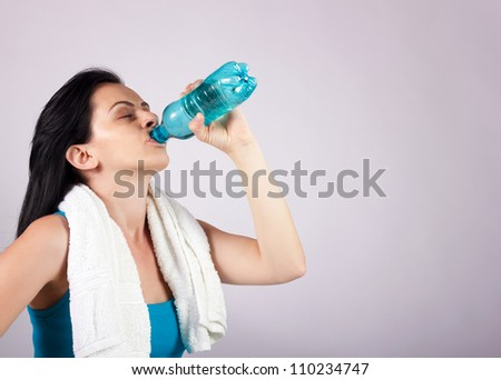 Portrait of young woman drinking water from plastic bottle with eyes closed.Brown background. - stock photo