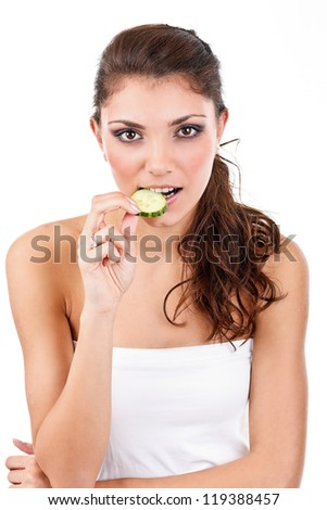 Portrait of young woman eating a slice of cucumber - stock photo