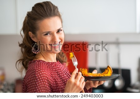 Portrait of young woman eating baked pumpkin in kitchen - stock photo