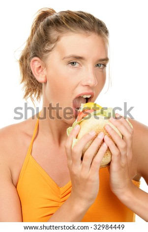 Portrait of young woman eating burger - stock photo