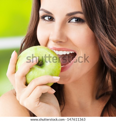Portrait of young woman eating green apple, outdoors - stock photo