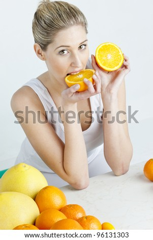 portrait of young woman eating orange - stock photo