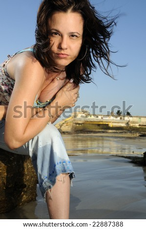 Portrait of young woman enjoying the summer breeze on the beach - stock photo