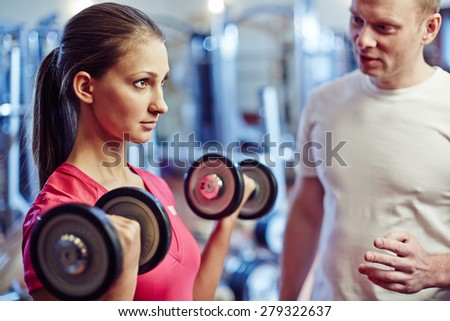 Portrait of young woman exercising with barbells in gym - stock photo