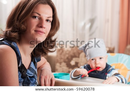 Portrait of young woman feeding her baby - stock photo