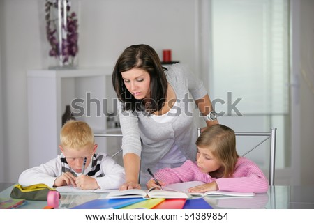Portrait of young woman helping a boy and a girl in doing homework - stock photo